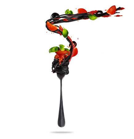 Concept vliegend voedsel met vork en traditionele Italiaanse sepia deegwaren met tomaat. Geïsoleerd op witte achtergrond Zeer hoge resolutie afbeelding