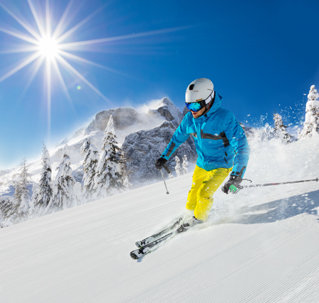 Young man skiing downhill in Alps. Beautiful clear blue sky. Winter sports and recreation.