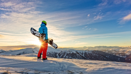 Snowboarder on the top of mountain, ready to downhill run off piste. European Alpine scenery in sunset light Stock Photo