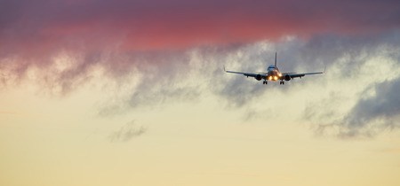 Commercial airplane jetliner landing in beautiful sunset light. Travel and business concept 스톡 콘텐츠