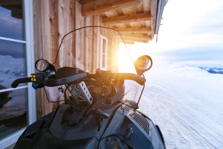 Closeup of snowmobile parking next to log cabin in mountains. Winter outdoor snow activities