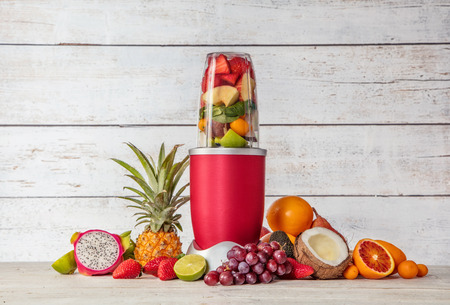 Smoothie maker mixer with pieces of fruit ingredients, placed in wooden interior. Healthy drink and lifestyle