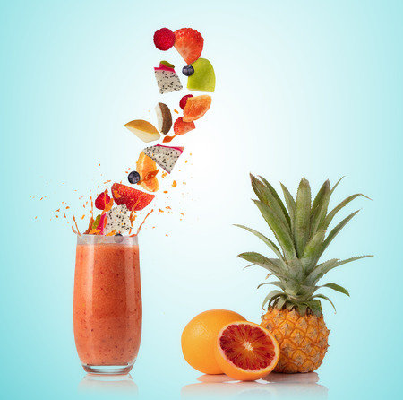 Smoothie drink with fruit flying ingredients, isolated on gradient background. Healthy drink and lifestyle Stock Photo