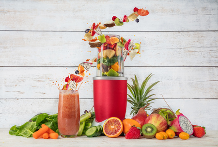 Smoothie maker mixer with fruit flying ingredients, placed in wooden interior. Healthy drink and lifestyle