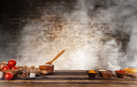 Baking ingredients placed on wooden table, ready for cooking. Copyspace for text. Concept of food preparation, brick wall on background.