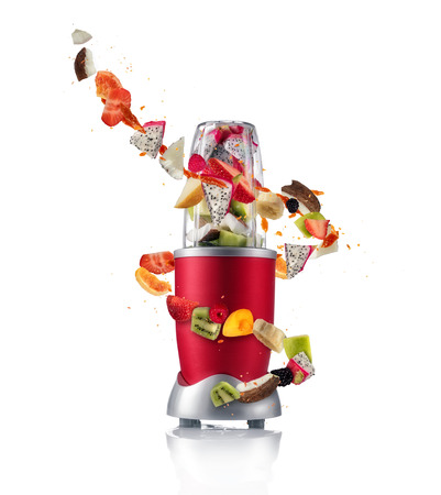 Smoothie maker mixer with pieces of fruit ingredients, isolated on white background. Healthy drink and lifestyle