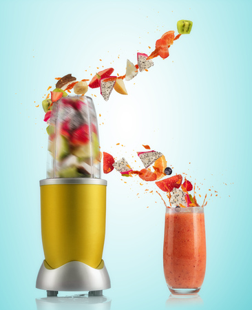 Smoothie maker mixer and glass with fruit flying ingredients, isolated on gradient background. Healthy drink and lifestyle