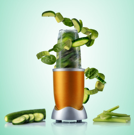 Smoothie maker mixer with vegetable flying ingredients, isolated on green background. Healthy drink and lifestyle
