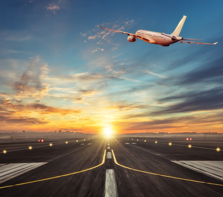 Commercial airplane flying above runway in sunset light. Travel and business theme.