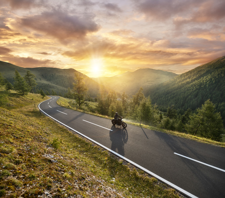 Motorbiker riding in Austrian Alps in beautiful sunset dramatic sky. Travel and freedom, outdoor activities