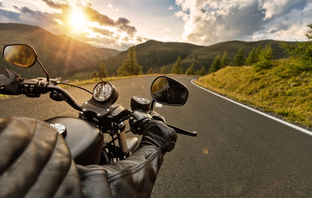 POV of motorbiker holding steering bar, riding in Alps in beautiful sunset dramatic sky. Travel and freedom, outdoor activities Stock Photo