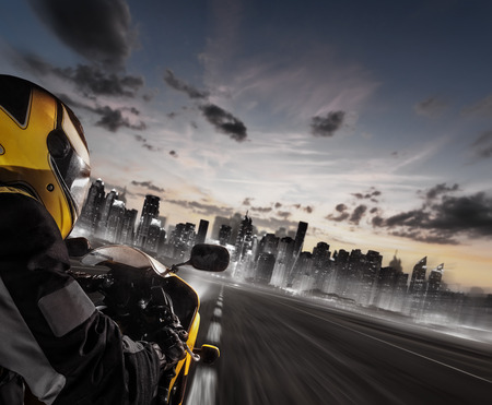 Supersport motorcycle rider heading to modern city skyline. Travel, speed, freedom and transportation topic.