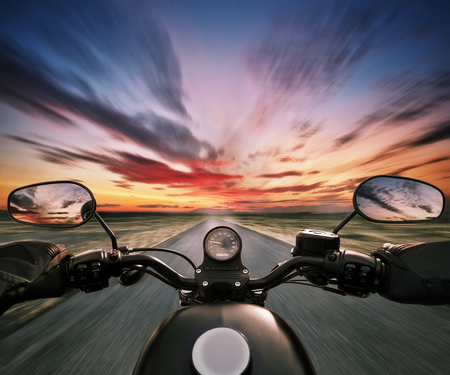 POV of motorbiker holding steering bar in beautiful sunset dramatic sky. Travel and freedom, outdoor activities. Motion blur Stock Photo