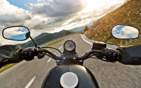 POV of motorbiker holding steering bar, riding in Alps in beautiful sunset dramatic sky. Travel and freedom, outdoor activities 写真素材