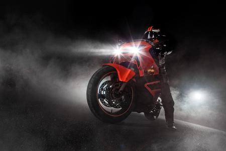 Supersport motorcycle driver at night with smoke around. Dark motorbike wallpaper