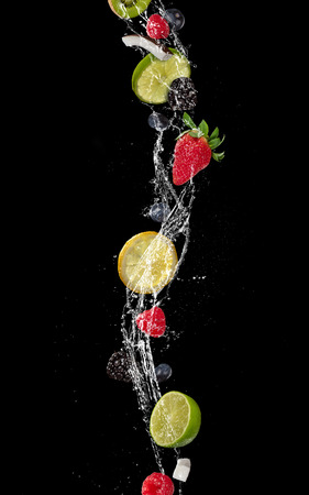Pieces of fruit with falling in water splash, isolated on black background. Stock Photo