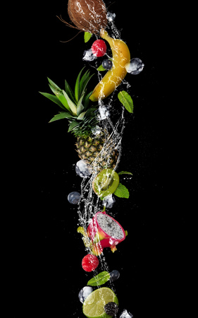 Pieces of fruit with mint leaves and ice cubes, falling in water splash, isolated on black background. Stock Photo