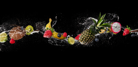Pieces of fruit with mint leaves and ice cubes, falling in water splash, isolated on black background. Stok Fotoğraf