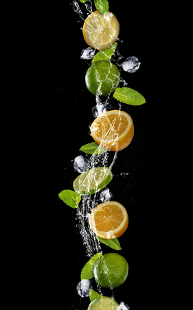 Slices of lime and lemon with mint leaves and ice cubes falling in water splash, isolated on black background