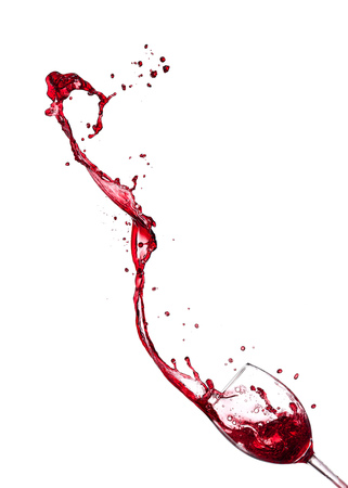 Red wine splashing from glass, isolated on white background. Stock Photo