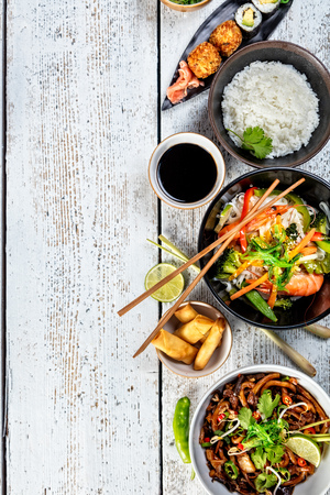 Asian food variation with many kinds of meals. Kari rice, noodles and vegetable. Top view, served on old wooden planks. Stock Photo