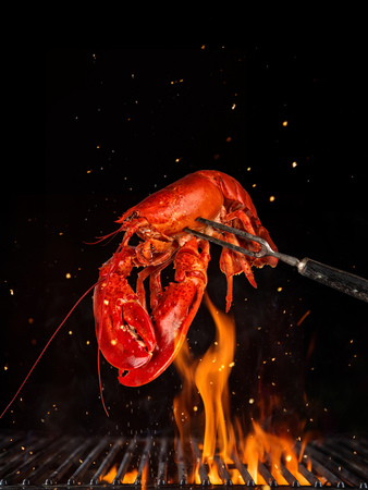 Flying whole lobster from grill grid, isolated on black background. Concept of flying food, very high resolution image 스톡 콘텐츠