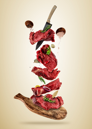 Flying pieces of raw beef steaks from cutting board, isolated on colored background. Concept of flying food, very high resolution image Stock Photo