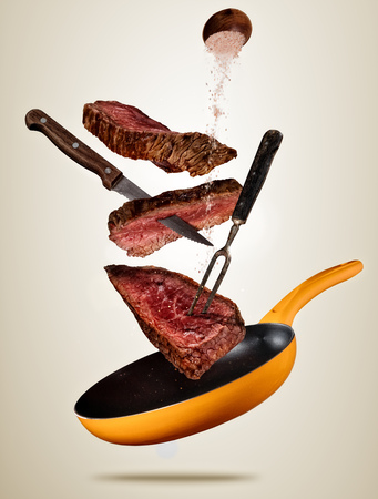 Flying pieces of beef steaks from pan, isolated on colored background. Concept of flying food, very high resolution image