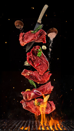 Flying pieces of raw beef steaks from grill grid, isolated on black background. Concept of flying food, very high resolution image Foto de archivo
