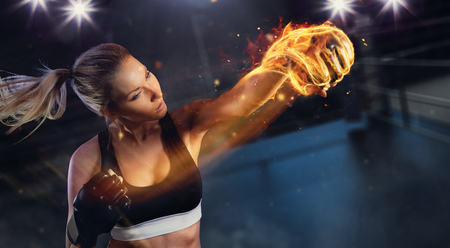Young blond woman with fire fist hitting the target. Concept of hard work and motivation, boxing arena on background. Very high resolution image