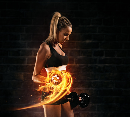 Attractive young blond woman doing bodybuilding, holding fire dumbbells. Concept of hard work and motivation, dark brick wall background. Very high resolution image Stok Fotoğraf