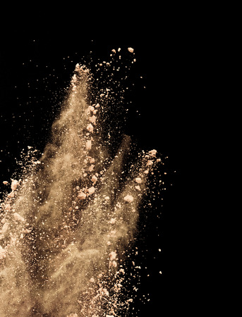 Abstract colored brown powder explosion isolated on black background. High resolution texture