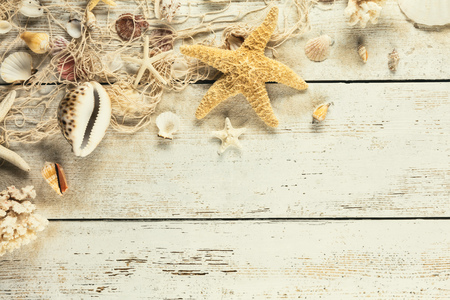 Seashells with fishing net placed on old wooden planks in vintage colors. Copyspace for text. Very high resolution image