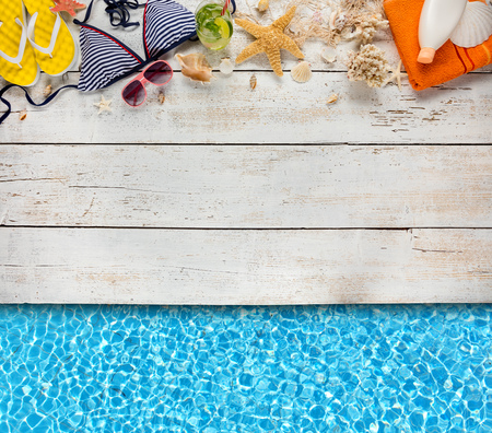 Beach accessories placed on white wooden planks with swimming pool water surface, top view. Summer holidays concept, free space for text. Very high resolution image Archivio Fotografico - 100508272