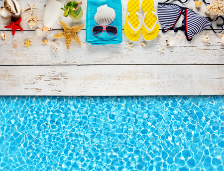 Beach accessories placed on white wooden planks with swimming pool water surface, top view. Summer holidays concept, free space for text. Very high resolution image Banco de Imagens