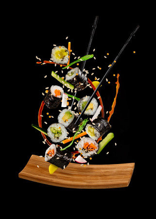 Flying sushi pieces isolated on black background. Concept of food levitation, high resolution image Standard-Bild - 101280227