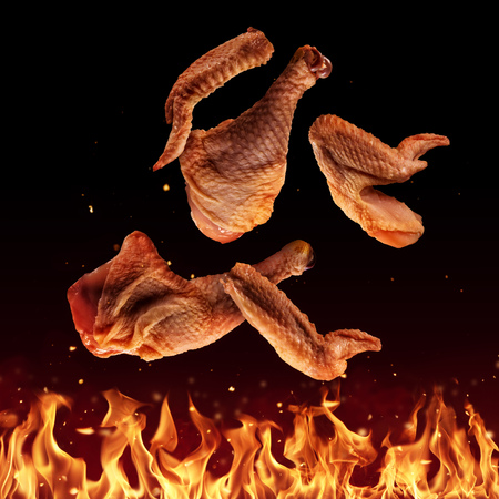 Flying raw chicken pieces above grill flames, isolated on black background. Concept of flying food, very high resolution image Banque d'images