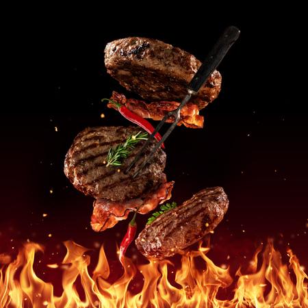 Fliegendes Rindfleisch gehackte Hamburgerstücke über Grillflammen, lokalisiert auf schwarzem Hintergrund. Konzept des fliegenden Essens, sehr hochauflösendes Bild Standard-Bild - 101648294