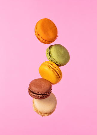 Colored french macarons flying in freeze motion. Concept of flying food isolated on pink background. High resoution image