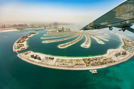 Aerial view from airplane window, artificial palm island in Dubai. Panoramic view.
