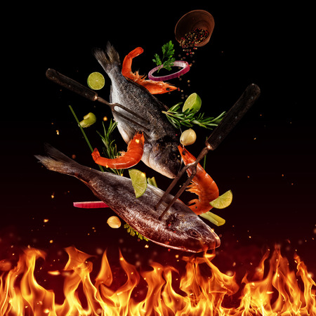 Flying raw sea bream fish above grill flames, isolated on black background. Concept of flying food, very high resolution image Stock Photo