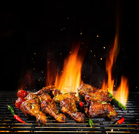 Delicious pieces of chicken meat on grill with Fire flames. Isolated on black background. Barbecue and grilling. Very high resolution image Foto de archivo - 104075797