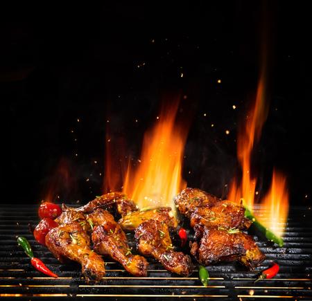 Deliziosi pezzi di carne di pollo alla griglia con fiamme di fuoco. Isolato su sfondo nero. Barbecue e grigliate. Immagine ad altissima risoluzione