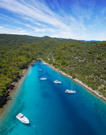 Sailing boats anchoring in Croatia bay, aerial view. Active life style, water transportation and marine sport.