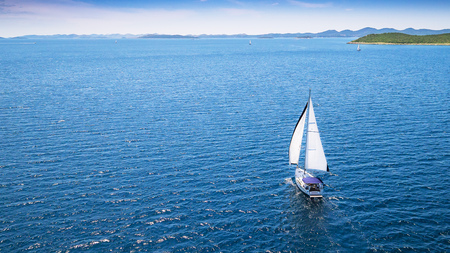 Sailing boat on open water, aerial view. Active life style, water transportation and marine sport. Фото со стока