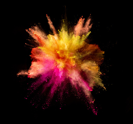 Explosion of coloured powder isolated on black background