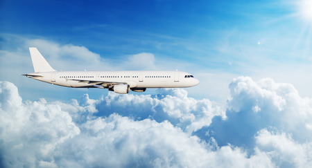 Commercial airplane jetliner flying above clouds. Transportaton and travel around the world. Fastest mode of transportation Stock Photo
