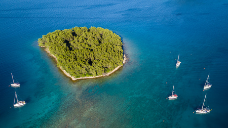 Aerial view of sailing boats anchoring next to small island, Croatia. Active life style, water transportation and marine sport. Banque d'images