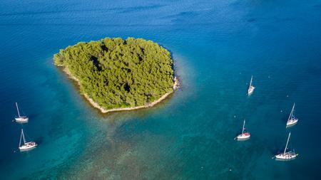 Vue aérienne de bateaux à voile ancrant à côté de petite île, Croatie. Style de vie actif, transport maritime et sport marin.
