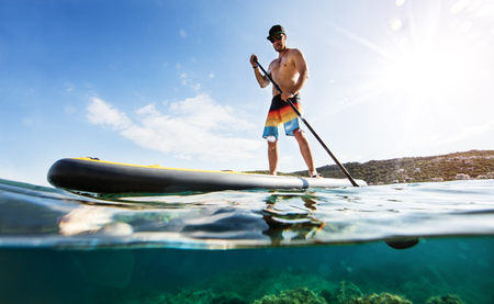 Young man on paddleboard, half under and half above water composition. Paddleboarding is the modern way of transportation and water activity sport. 스톡 콘텐츠 - 105126047